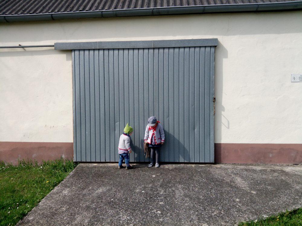 bub und mädchen vor garagentor zum thema rabenmutter